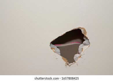 A closeup of a hole in the wall with electrical wire.