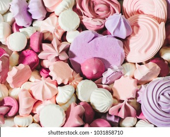 Closeup of home baked pink and violet meringues cookies with sugar. Homemade meringue kisses.