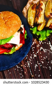 Closeup of home made beef burger with lettuce and potato served on stone cutting board. Dark wooden background