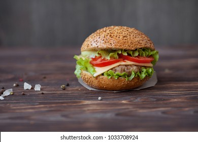 Closeup of home made beef burgers with lettuce and mayonnaise served on little wooden  board. Dark background