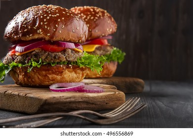 Closeup of home made beef burgers with lettuce and mayonnaise served on little wooden cutting board. Dark background