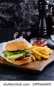Closeup of home made burgers on wooden background, classic burger with beef patty and french fries copyspace