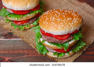 Closeup of home made burgers on wooden background.