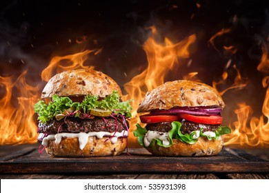 Close-up of home made burgers on wooden table.