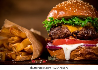 Close-up of home made tasty burger with french fries on wooden table.