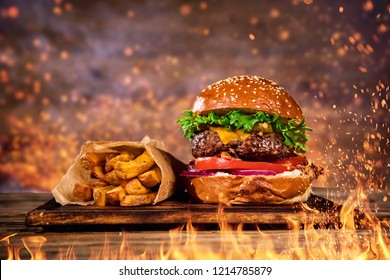 Close-up of home made tasty burger with french fries and fire flames.