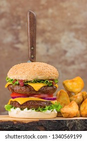 Close-up of home made tasty double burger on wooden table.