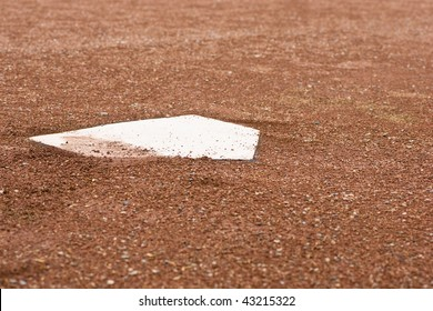 A closeup of home plate with surrounding reddish brown gravel at a baseball diamond.