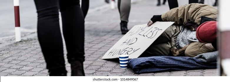 Close-up of homeless and hungry street person asking for help on the sidewalk