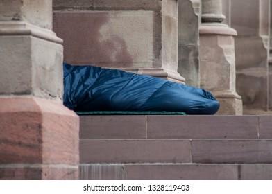 closeup of homeless people sleeping in the street in sleeping bag