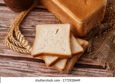 Close-up of homemade bread. Peasant square bread and wheat spikelets with space for text. Homemade baking. White bread with flour and milk on wooden chopping board wheat rye ears copy space.
