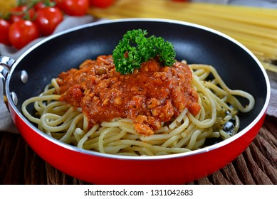 Closeup of homemade spaghetti bolognese in frying pan. Decorated with cherry tomatoes, ingredients on background. Concept about food preparation in the kitchen. Homemade Cooking