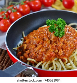 Closeup of homemade spaghetti bolognese in frying pan. Decorated with cherry tomatoes, ingredients on wooden background. Concept about food preparation in the kitchen in square size. Square ratio,1:1
