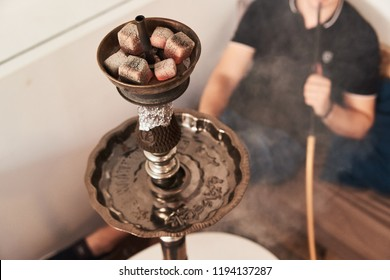 Close-up of hookah with red coconut coal and man smoking shisha at lounge bar on background.