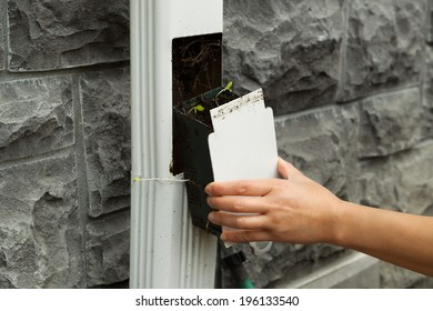 Closeup horizontal photo of female hand pulling out house gutter filter with stone wall in background