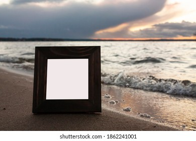 Close-up horizontal photo of a single dark brown wooden squre empty frame for photo on a sea shore with cloudy sky on the background