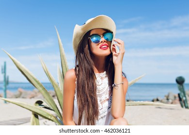 Close-up horizontal portrait of attractive brunette girl with long hair sitting on the beach near cactus on the background. She wears hat, sunglasses and white shirt She is smiling far away.
