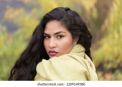 Closeup horizontal portrait of sultry hispanic young woman with long curly dark hair wearing pale green scarf in front of soft focus Fall foliage