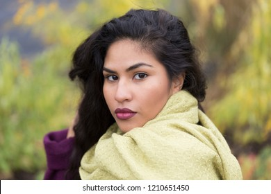 Closeup horizontal portrait of sultry hispanic young woman with right hand in her long curly dark hair wearing pale green scarf in front of soft focus Fall foliage