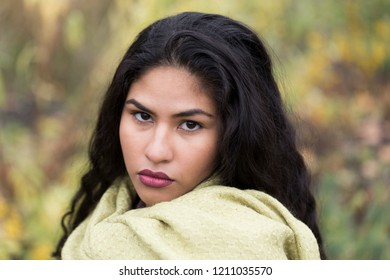 Closeup horizontal portrait of sultry hispanic young woman with serious expression wearing pale green scarf in front of soft focus Fall foliage