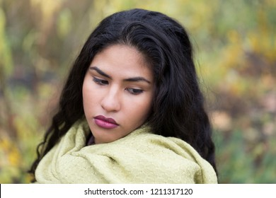 Closeup horizontal portrait of sultry hispanic young woman with long curly dark hair looking down demurely and wearing pale green scarf in front of soft focus Fall foliage