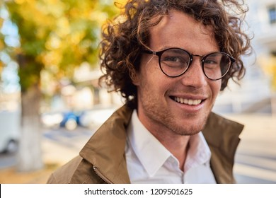 Closeup horizontal portrait of young happy business man with glasses smiling and posing outdoors. Male student in autumn street. Smart guy in casual wears spectacles with curly hair walking on street