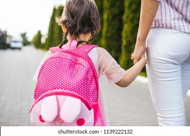 Closeup horizontal rear view of mother and little girl preschooler eith backpack go hand in hand to the kindergarten. Mom and her child walking on the street. Beginning of lessons. Togetherness