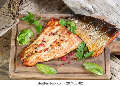 Closeup horizontal view of smoked salmon fillets with seasoning inside of drift wood on serving board