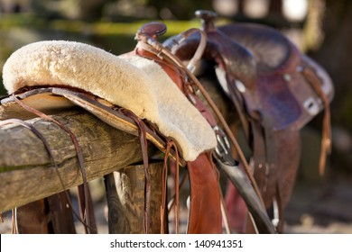Close-up of a horse saddle on top of a wooden fence of the paddock