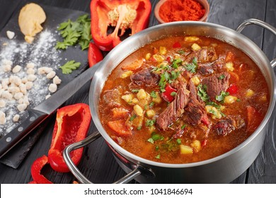 close-up of  hot beef hungarian goulash  or bograch soup with paprika, small egg pasta, vegetables and spices in a pot. ingredients and soup ladle on table, classic recipe, view from above, close-up