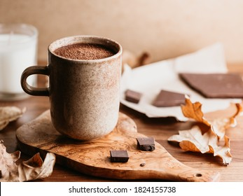 Close-up of hot chocolate in a ceramic mug on the table. Autumn or winter cozy still life.