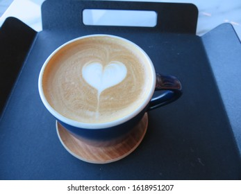 Closeup of a hot coffee latte with a distinct heart-shaped foam art decoration
