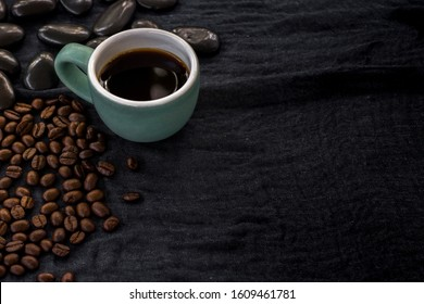 Close-up of a hot cup of coffee and coffee beans on the fabric