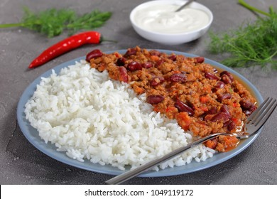close-up of hot delicious chili con carne with red kidney beans served on plate with boiled rice on concrete table with sour cream, horizontal view from above