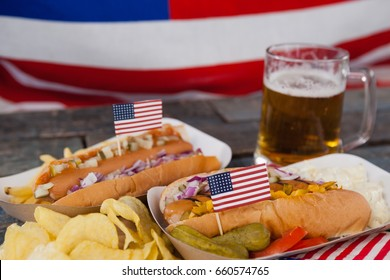 Close-up of hot dog and glass of beer with american flag on wooden table