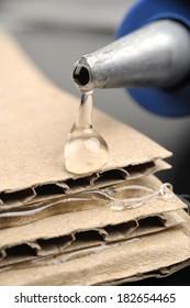closeup hot glue gun apply the glue to corrugated cardboard