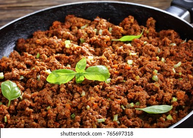 close-up of hot juicy ground beef stewed with tomato sauce, spices, basil, finely chopped vegetables and celery in frying pan, classic recipe, side view from above