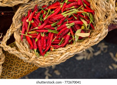 Close-up of hot red Chile Peppers in a basket at open air market in Italy.
