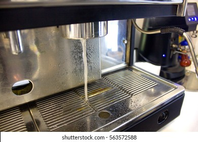 closeup of hot water running from the coffee machine