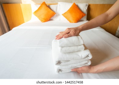Closeup of hotel maid arranging the stack of towels on bed. Conceptual of female chambermaid making bed in hotel room.