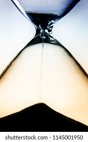 Close-up of an hourglass with dark sand falling through silhouette