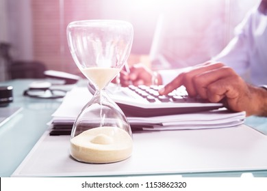 Close-up Of Hourglass In Front Of Businessperson's Hand Calculating Invoice Using Calculator