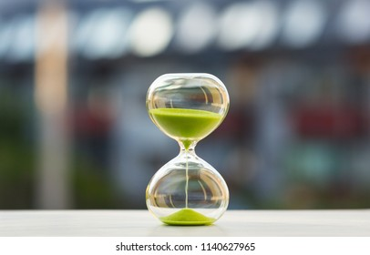 Close-up, hourglass with green sand on a blurred background