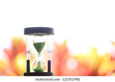 Close-up of the hourglass Light from a variety of natural colors to the background selective focus and shallow depth of field