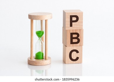 Close-up of an hourglass next to wooden blocks with the text PBC. PBC - text in wooden building blocks, white backgrounds.