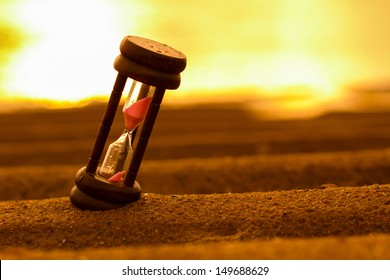 Closeup of hourglass on the sand.Timer Beach Sunrise