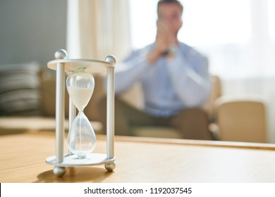 Closeup of hourglass on table with blurred shape of man waiting in background, copy space