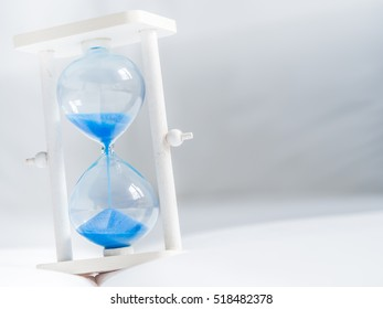 Closeup of hourglass on white fabric texture