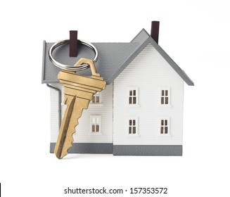 Closeup of house and key isolated on white background. Concept of real estate. Clipping path included.