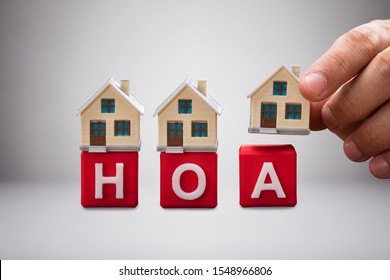 Close-up Of House Miniature Models Over Red Homeowner Association Wooden Blocks Against White Background